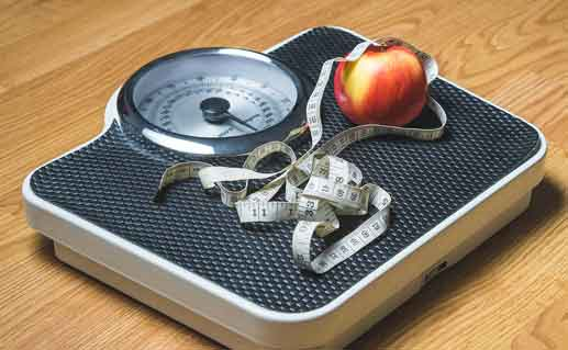 Scale with measuring tape and an apple.