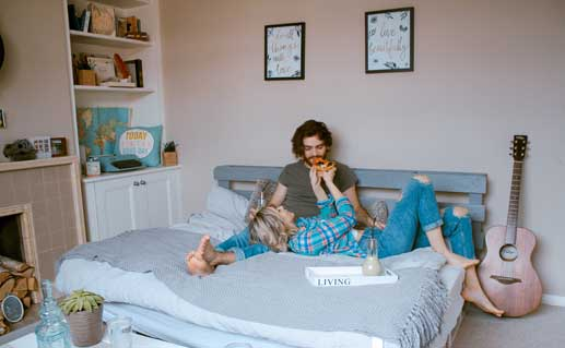 Couple in bedroom eating breakfast in bed.