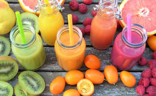 Colorful juices in glasses among fruits.