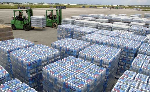 Pallets of bottled water in skids at an airport.