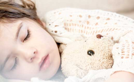 Child sleeping while holding a teddy bear.