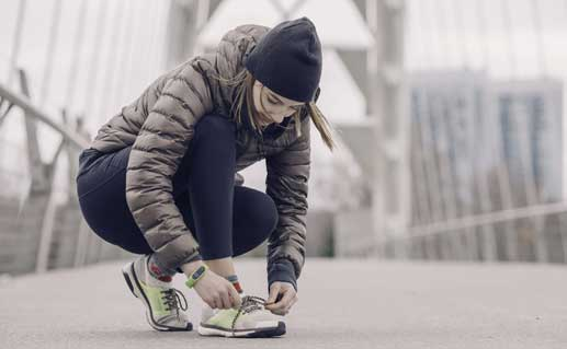 Woman lacing up her sneakers while on a run.