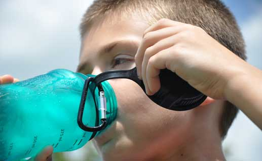 Boy drinking water from water jug.
