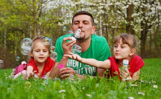 Father with two daughters blowing soap bubbles in a park.
