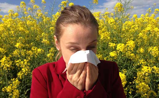Woman sneezing into a tissue with flowers behind.