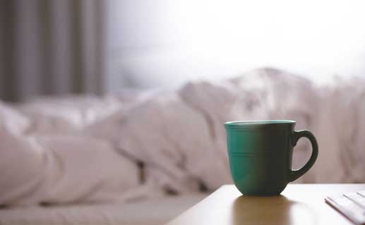 Coffee mug in night table next to bed.