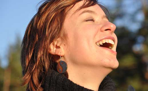 Woman laughing outdoors during sunset.